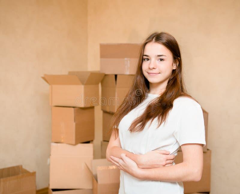 Tonårigt flickaanseende på en bakgrund av kartonger royaltyfri fotografi