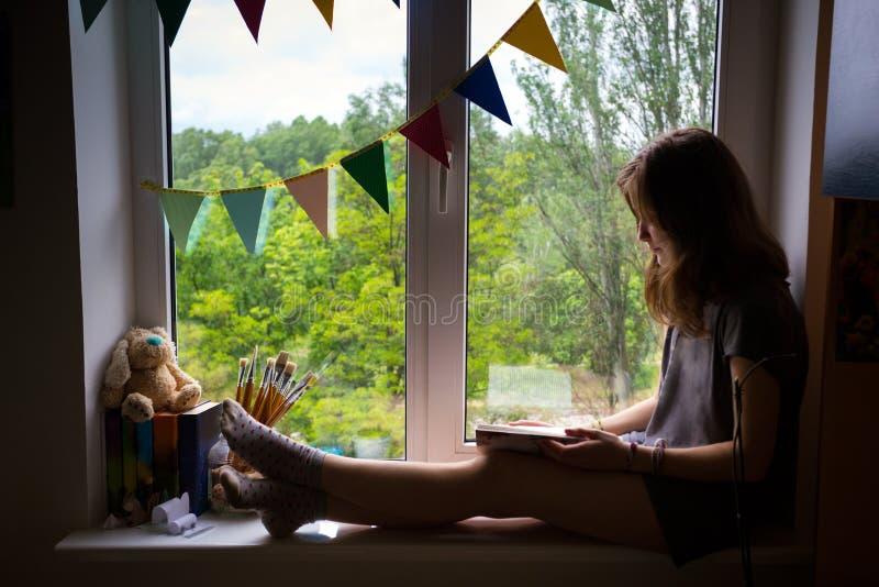 Tonårigt flickasammanträde på en fönsterbräda royaltyfria bilder