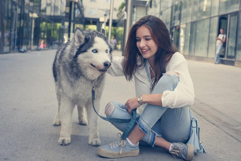 Tonårigt flickasammanträde på trottoaren med hennes hund royaltyfri fotografi
