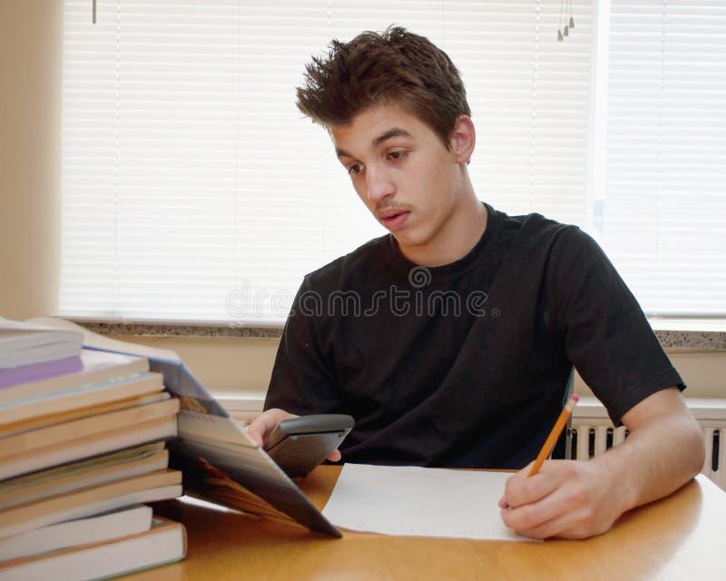 Tonårigt göra hans läxa arkivbilder