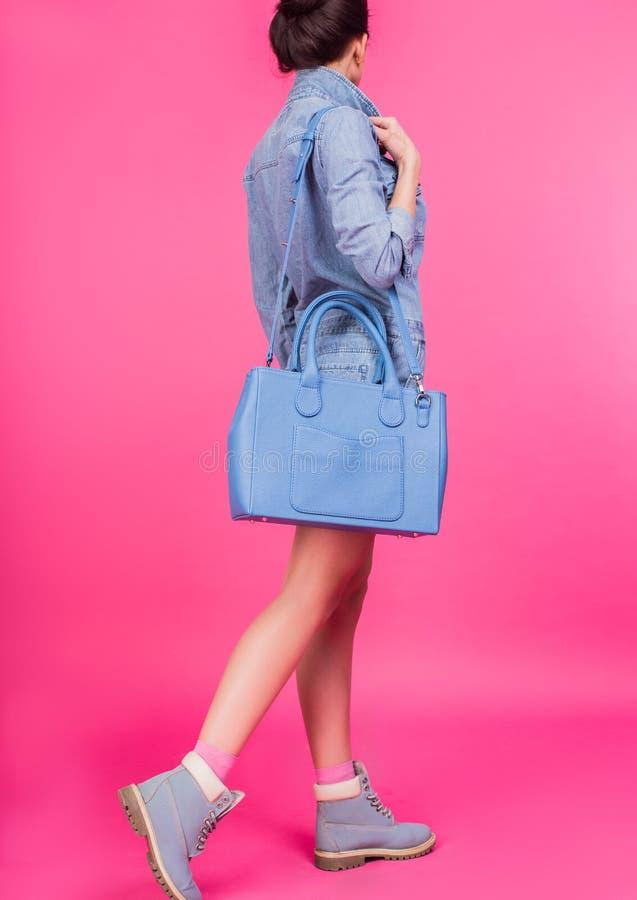 Tonårigt i blåa kängor och blått för grov bomullstvilldräktinnehav piska handväskan royaltyfri foto