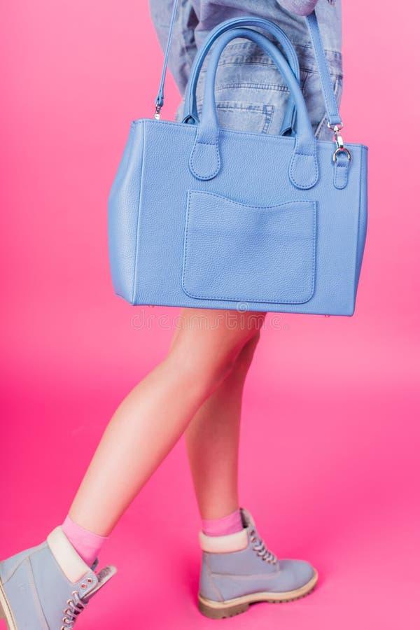 Tonårigt i blåa kängor som rymmer handväskan på en rosa bakgrund arkivbild