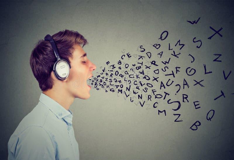 Tonårigt i hörlurar som sjunger på grå färger fotografering för bildbyråer