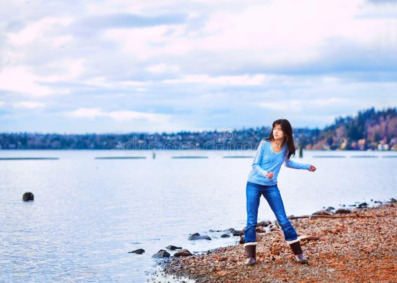 Tonårigt kasta för flicka vaggar i vattnet, längs en stenig sjökust royaltyfria bilder