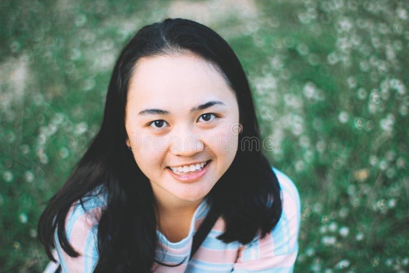 Tonårigt leende för asiatisk flicka på lyckligt leende för blommafält royaltyfri foto