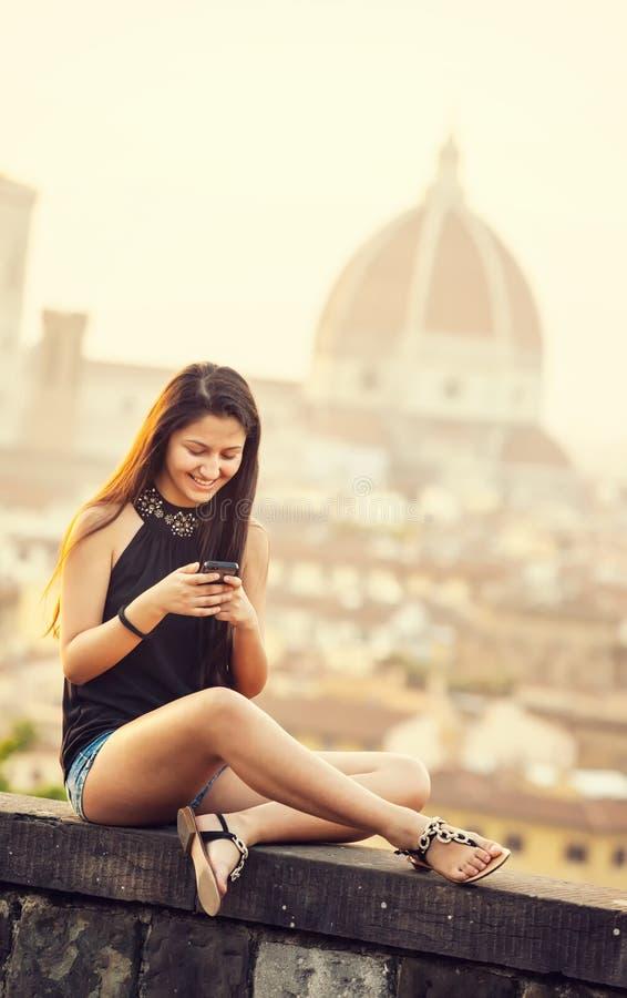 Tonårigt på solnedgången i Florence använder smartphonen royaltyfria foton