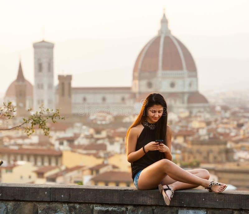 Tonårigt på solnedgången i Florence använder smartphonen arkivbilder