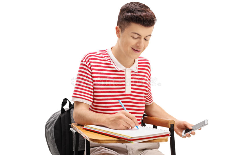 Tonårigt studentfusk på ett prov med en telefon royaltyfri bild