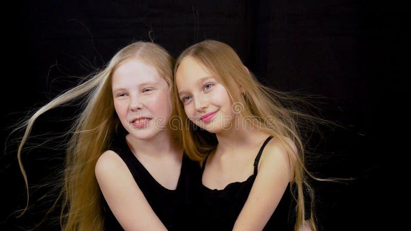Tonåring för två flicka som poserar på svart bakgrund i studio och hår som på flyttar vind arkivbilder
