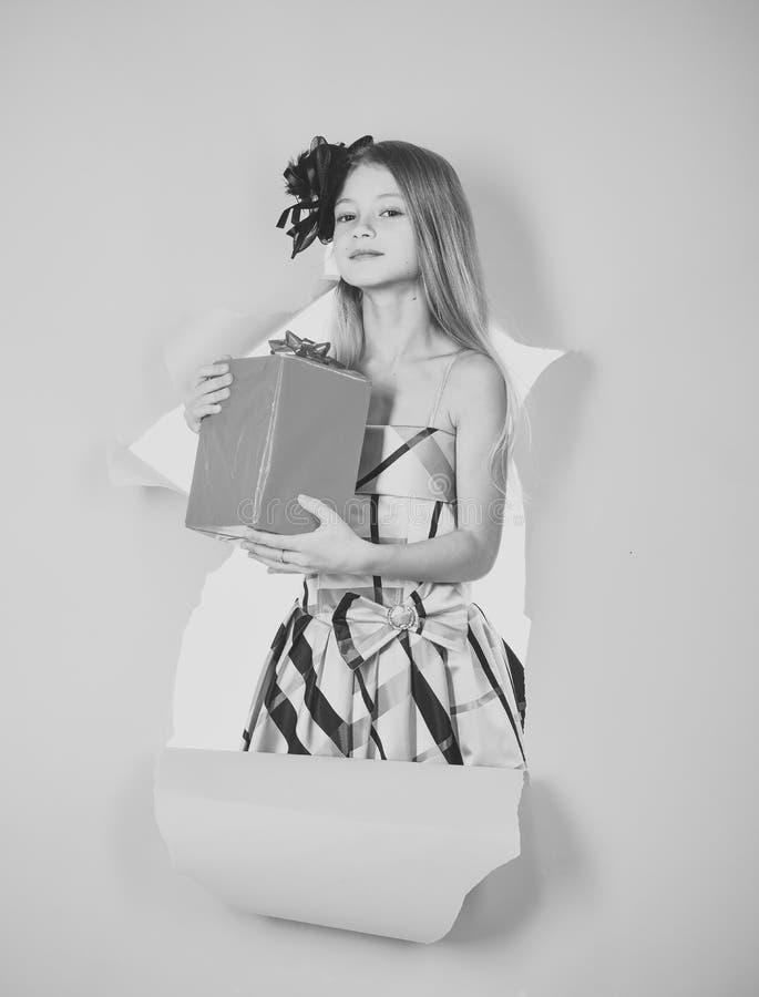 Tonåring med en gåva Lycklig blond flicka som öppnar en gåva, födelsedag royaltyfria foton