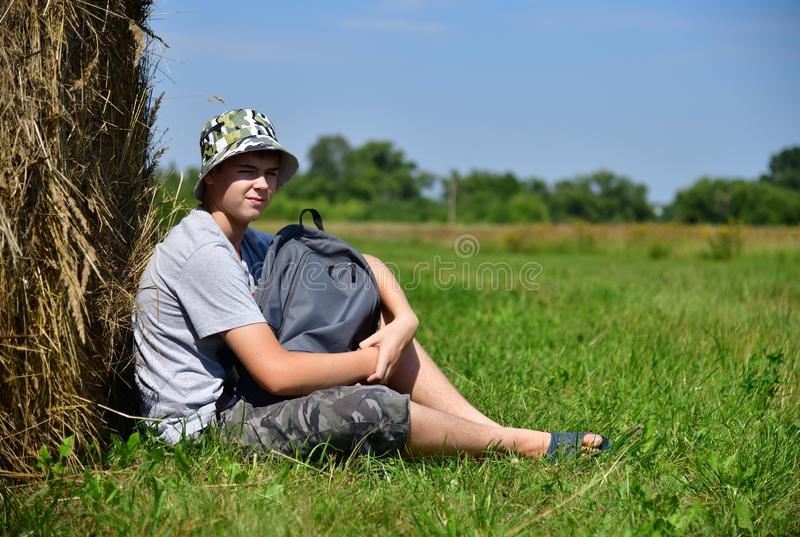 tonåring med ryggsäcksammanträde bredvid bunt av sugrör fotografering för bildbyråer