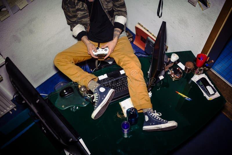 Tonåring med videospelböjelse som spelar, medan sitta på mig fotografering för bildbyråer