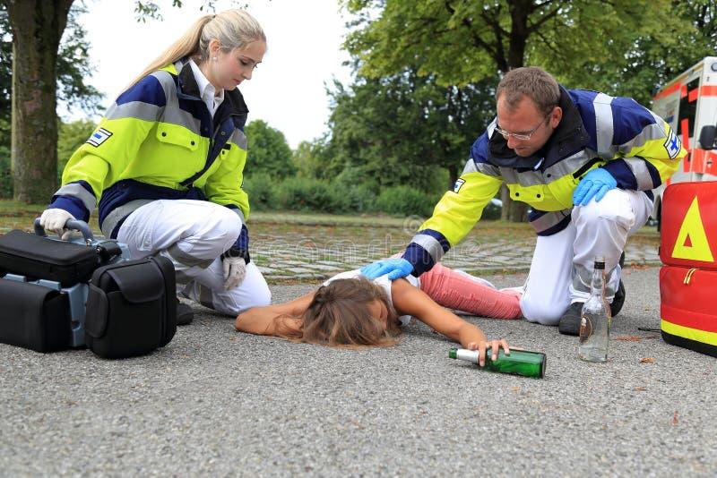 Tonåring som är full på golv med personen med paramedicinsk utbildning royaltyfri fotografi
