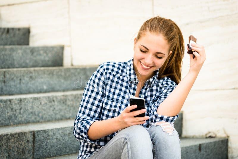 Tonåring som äter chcolate som ser i telefon arkivbilder