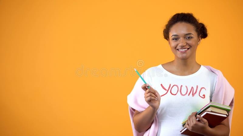 Tonåring som poserar på kameran med böcker, internationell studentutbildningssystem arkivbilder