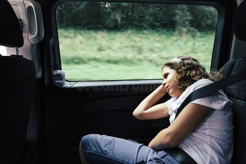 Tonåring som sover i backseaten av en bil på en tur royaltyfria foton