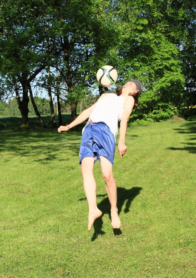 Tonåring som spelar fotboll med bröstkorgen arkivfoto