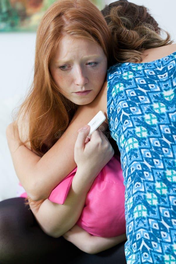 Tonåring som tröstar den gravida vännen royaltyfri bild