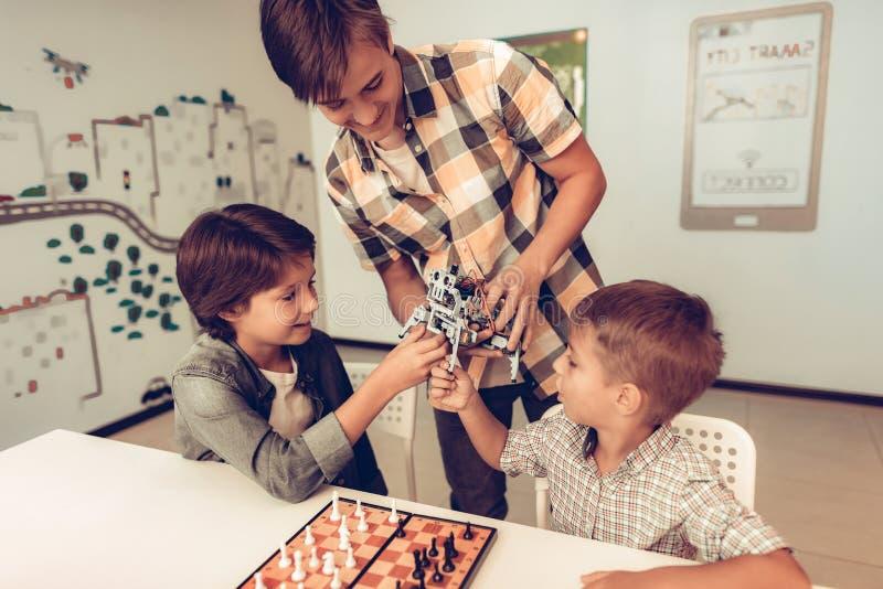 Tonåring som visar roboten till två sittande pojkar fotografering för bildbyråer
