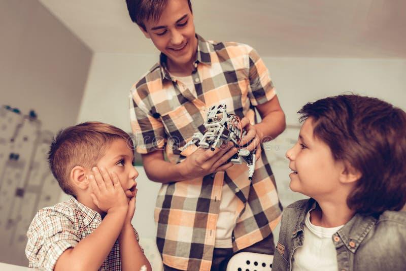Tonåring som visar roboten till två sittande pojkar arkivfoto