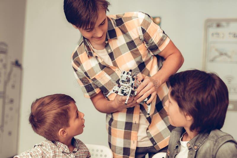 Tonåring som visar roboten till två sittande pojkar royaltyfria foton