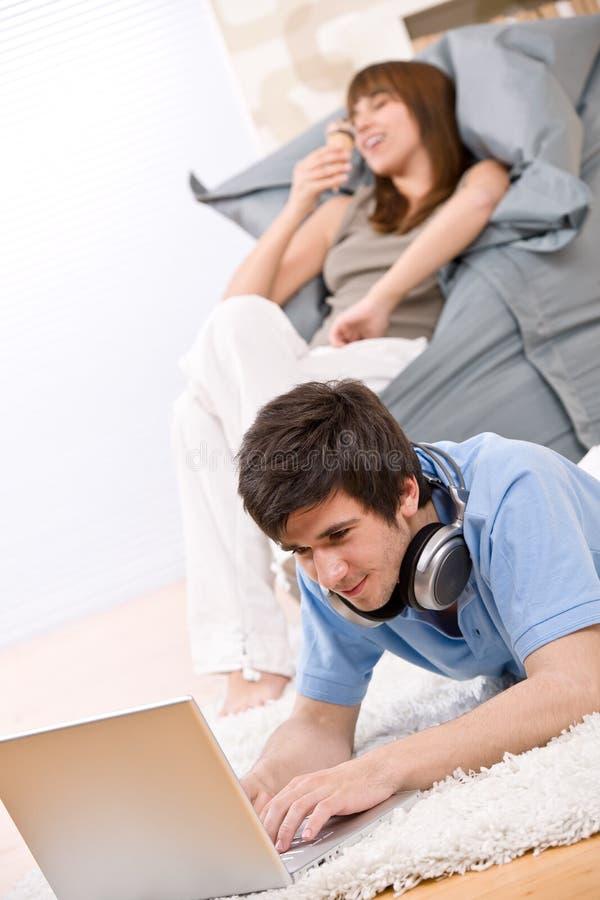 tonåring två för hörlurarbärbar datordeltagare arkivbilder
