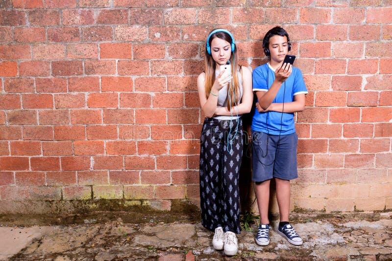 Tonåring två med Smartphones arkivbild