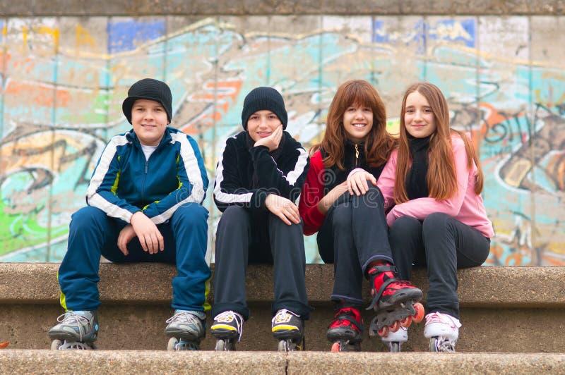 tonåringar för skridskor för lycklig rulle för grupp sittande royaltyfria bilder