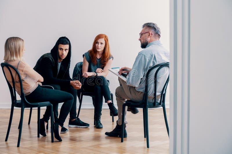 Tonåringar i gruppterapi för böjelse med en psykiater fotografering för bildbyråer