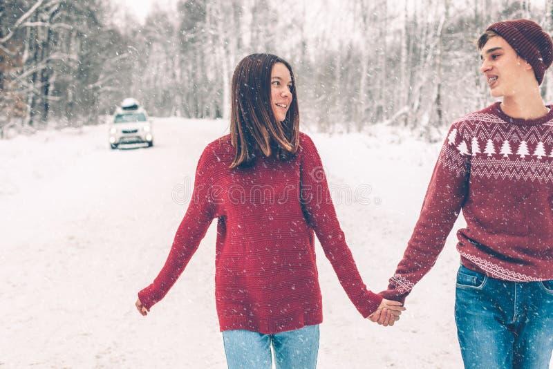 Tonåringar i jultröjor som går i insnöad vinter fotografering för bildbyråer