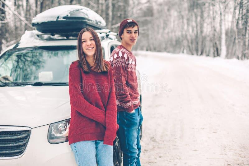 Tonåringar i jultröjor som går i insnöad vinter royaltyfri foto