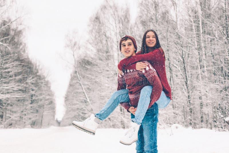 Tonåringar i jultröjor som spelar i insnöad vinter royaltyfri fotografi