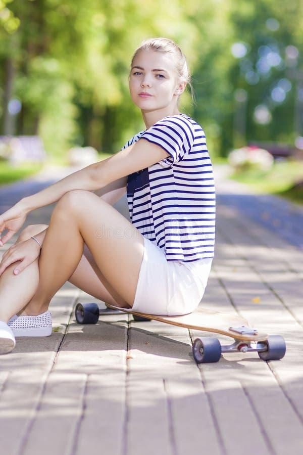 Tonåringar livsstil, begrepp och idéer Den blonda Caucasian flickan som poserar med Longboard parkerar in, utomhus fotografering för bildbyråer