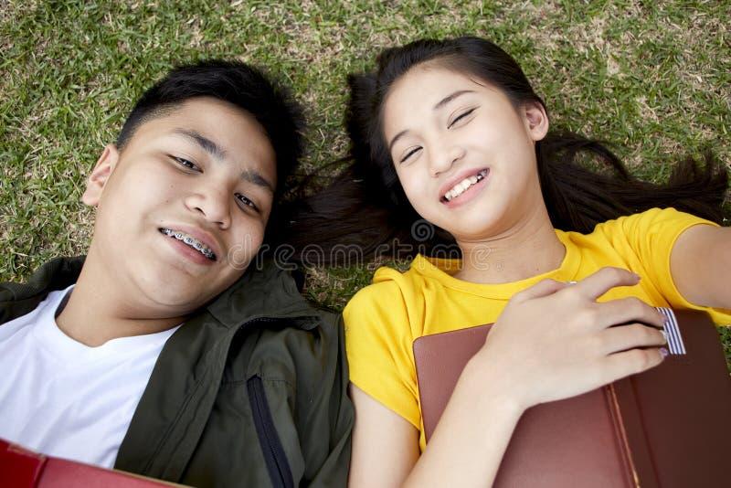 Tonåringar med böcker som ligger på grönt gräs arkivbild