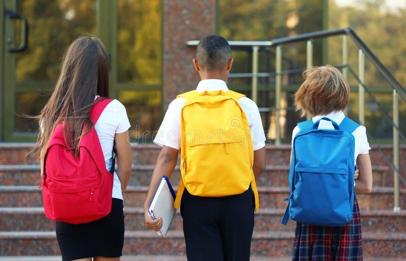 Tonåringar med den near skolaingången för färgglade ryggsäckar arkivbilder