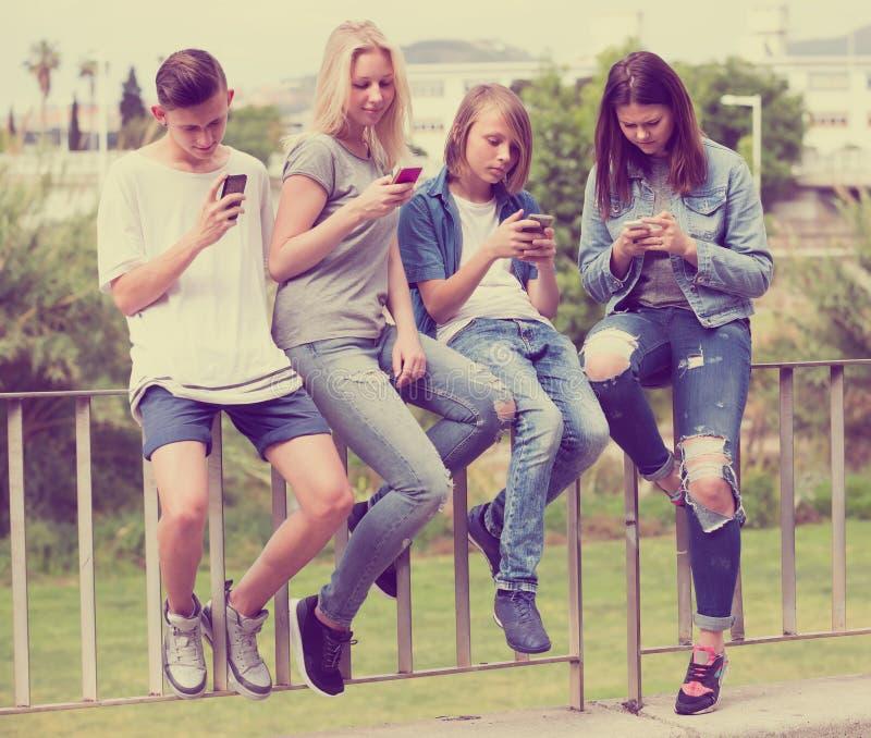 Tonåringar med telefoner parkerar in fotografering för bildbyråer