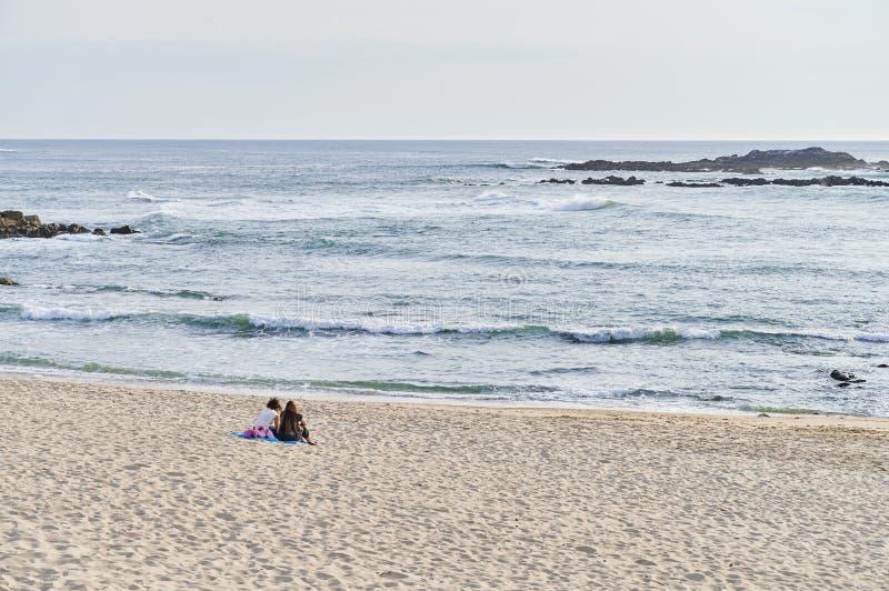 Tonåringar placerade samtal bara på stranden royaltyfri bild