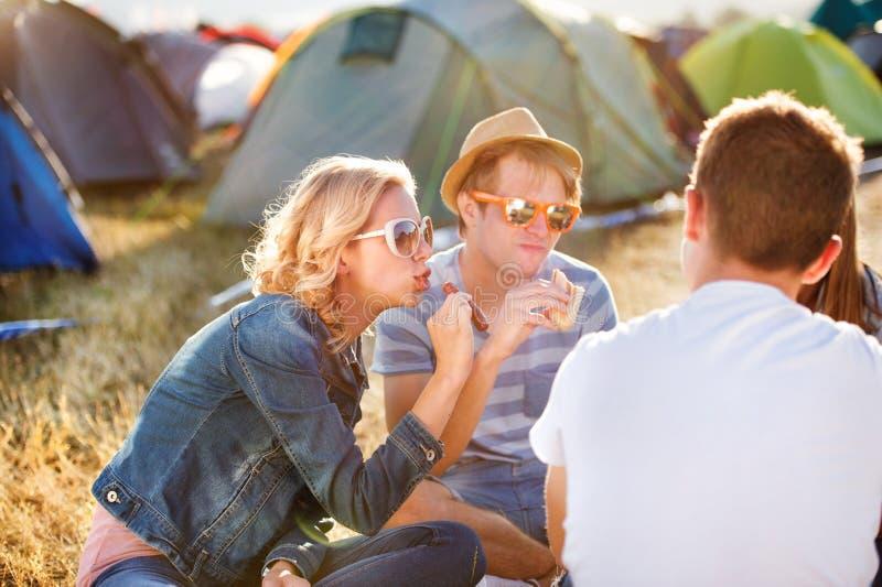 Tonåringar som framme sitter på jordningen av tält och att äta royaltyfri fotografi