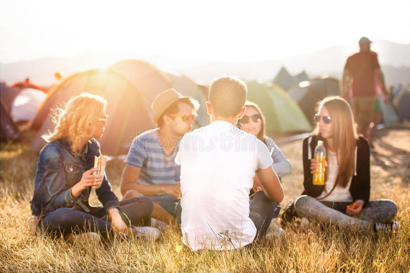 Tonåringar som framme sitter på jordningen av tält och att äta fotografering för bildbyråer