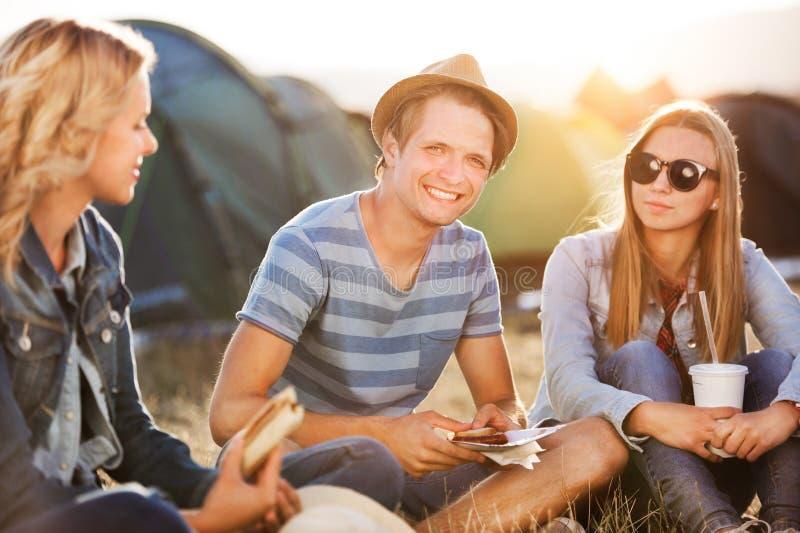 Tonåringar som framme sitter på jordningen av tält och att vila royaltyfri fotografi