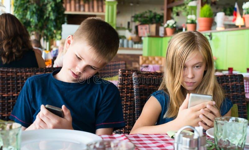 Tonåringar som har gyckel med mobiltelefoner i kafé Modernt livsstil och teknologibegrepp Barn som sitter i restaurang och arkivbilder