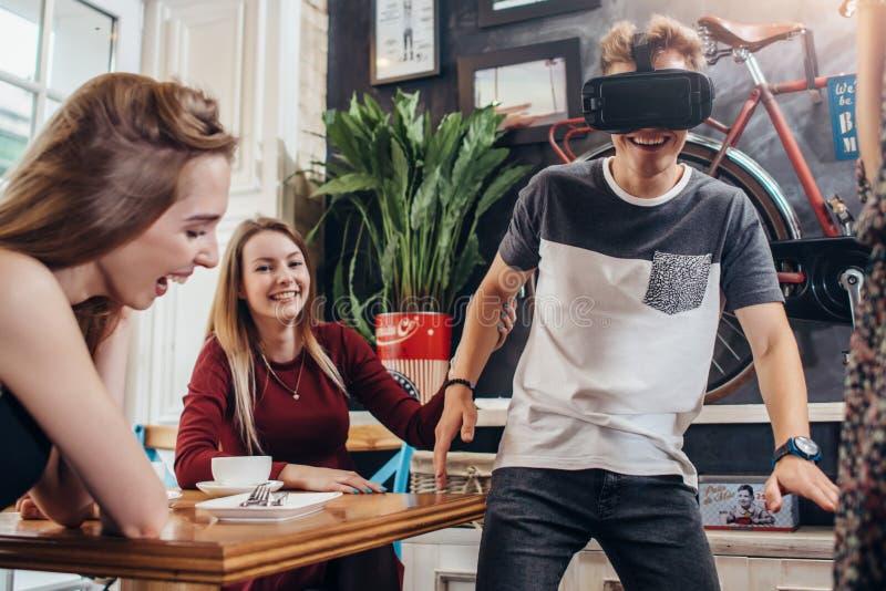 Tonåringar som passerar fritid, genom att testa virtuell verklighethjälmen som hemma spelar roliga lekar arkivbilder