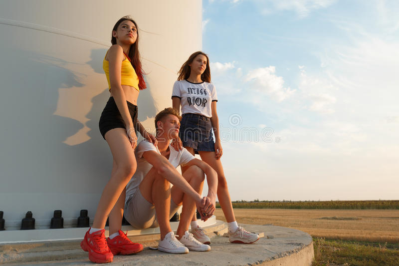 Tonåringar som sitter nära en väderkvarn på en bakgrund för blå himmel Två varma flickor och en stilig grabb ungdombegrepp kopier royaltyfri foto