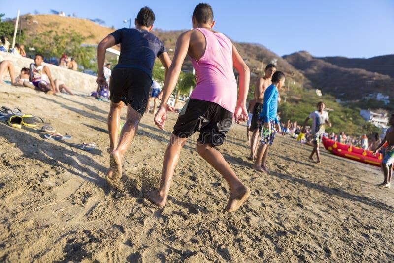 Tonåringar som spelar på stranden av Taganga i Colombia royaltyfri bild