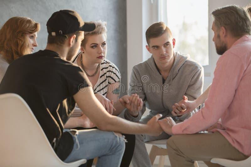 Tonåringar som talar med böjelselägerledaren arkivbilder