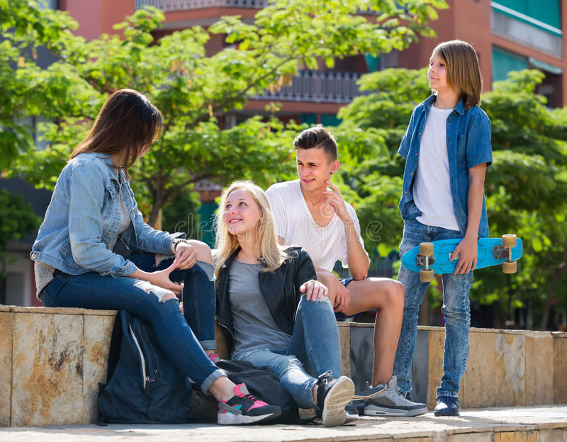 Tonåringar som utomhus pratar i stad royaltyfri bild