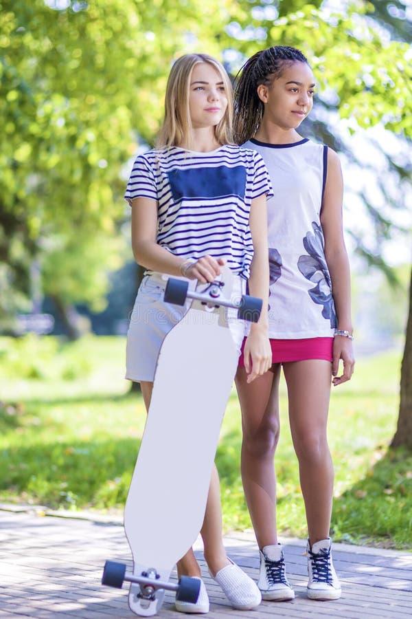 Tonåringbegrepp Två tonårs- flickvänner samman med Longboard i parkerar utomhus fotografering för bildbyråer
