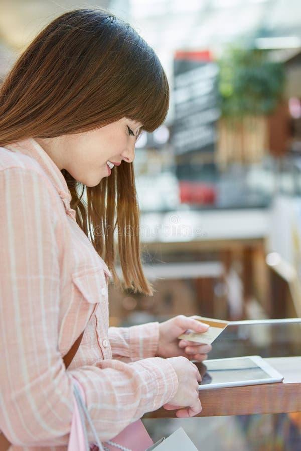 Tonåringen använder kreditkorten och minnestavlan royaltyfria foton