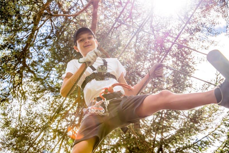 Tonåringen med handlingkameran som har gyckel på höga rep, jagar, äventyrar parkerar och att klättra träd i skog royaltyfri foto