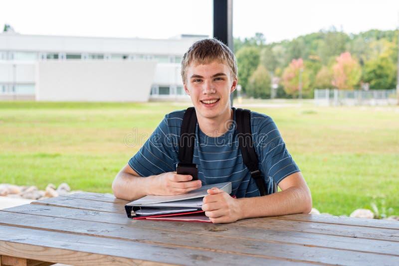 Tonåringen som utomhus studerar i, parkerar fotografering för bildbyråer
